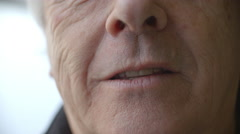 Extreme close up of a senior woman's mouth changing shape as she smiles Stock Footage