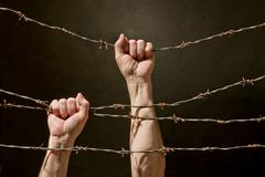 Hand behind barbed wire Stock Photos