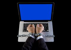 Hands businessman addicted to work bond to computer with iron chain - stock photo
