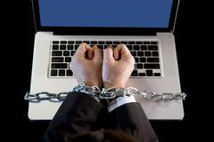 Hands businessman addicted to work bond to computer with iron chain Stock Photos