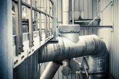 Detail of building exterior and piping at industrial plant Stock Photos