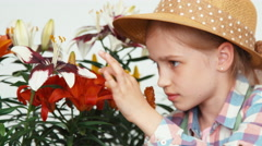 Close-up portrait flower-girl child sitting near flowers and eating lollipop - stock footage