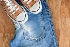 Sneaker and jeans isolated on wooden background Stock Photos