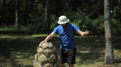 A man climbs on a large wooden cone and shoots himself in the action camera Stock Footage