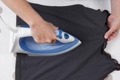 High angle view of woman ironing on ironing board Stock Photos