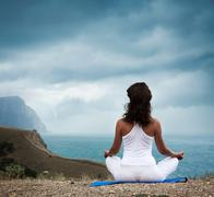 Woman Practicing Yoga at Stormy Sea - stock photo
