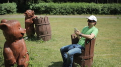 Male tourist touches the phone near a wooden bear. In the summer the lawn is - stock footage