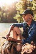 Senior hiker sitting by a lake on summer day Stock Photos