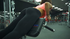 Back view female does hyperextension at the gym slow motion Stock Footage
