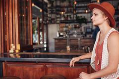 Beautiful young woman sitting alone at bar counter Stock Photos