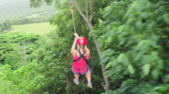 Joyous young girl smiling and having fun while zipling above lush rainforest Stock Footage