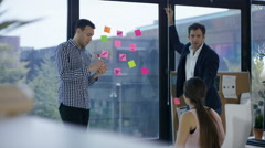 4K Business team in modern office brainstorming with coloured notes on window Stock Footage