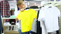 Cute smiling boy stands near clothes and choosing Stock Footage