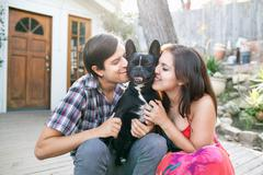 Young couple sitting on patio snuggling up to dog Stock Photos