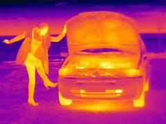 Thermal image of woman kicking automobile tire on roadside Stock Photos