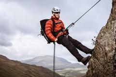 Young male climber abseiling down rock, The Lake District, Cumbria, UK - stock photo