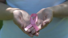 Woman holding pink awareness ribbon in hands - stock footage