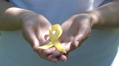 Woman holding yellow awareness ribbon in hands Stock Footage