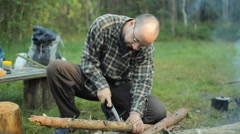 Man sawing a small tree camp saw. Near lit a fire and lay the tourist stuff - stock footage