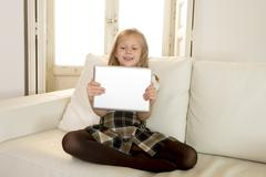 sweet blond female child on couch using internet app on digital tablet - stock photo