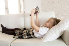Sweet blond female child on couch using internet app on digital tablet Stock Photos