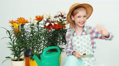 Close-up portrait flower-girl child sitting near flowers and watering can Stock Footage