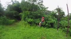 Young girl having fun while riding zipline cable upside down Stock Footage