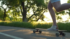 Close up male legs riding longboard in sun light slow motion Stock Footage