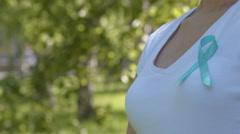 Girl wearing teal awareness ribbon - stock footage