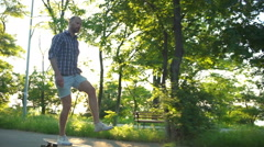 Handsome male riding longboard in park on sunny day slow motion Stock Footage