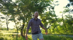 funny male grimacing while riding longboard in park slow motion - stock footage