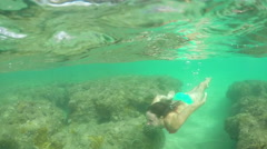 SLOW MOTION: Young girl swimming in shallow waters above amazing coral reefs Stock Footage