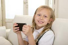 Happy blond little girl on home sofa using internet app on mobile phone Stock Photos