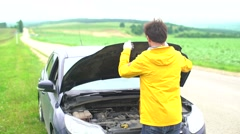Angry man swears and try to fix a broken car Stock Footage