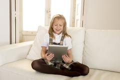 sweet cute female child on couch using internet app holding digital tablet - stock photo
