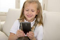 sweet blond female child on couch using internet app on mobile phone - stock photo