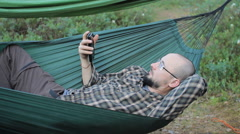A man in a hammock touch phone. Man in the woods with a beard and glasses Stock Footage