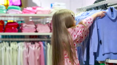 Fashionable shop. little girl in a clothing store. chooses a suit Stock Footage
