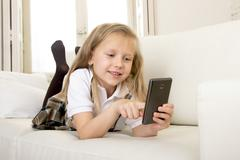 Sweet blond female child on couch using internet app on mobile phone Stock Photos