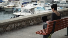 Woman with short black hair working on the laptop outdoor near the harbour - stock footage