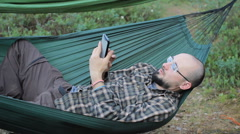 A man in a hammock is video calling on the phone. Man in the woods with a beard Stock Footage
