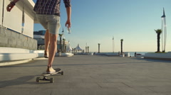 Guy on longboard holding bottle of water gives five to another guy slow motion Stock Footage