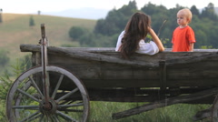 Baby son and young mother in wooden cart, relaxing in nature - stock footage
