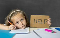 Sad and tired cute junior schoolgirl with blond hair sitting in stress working Stock Photos