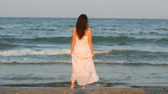 Beautiful woman on seashore, long hair in the breeze, water sea touch bare feet Stock Footage