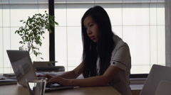 Asian businesswoman working in modern office on the background big windows Stock Footage