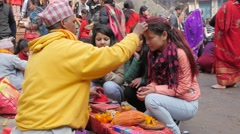 Girls get Tilaka mark on forehead by hindu priest,Dakshinkali,Nepal - stock footage