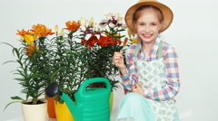 Close-up portrait flower-girl sitting near flowers and watering can and eating Stock Footage