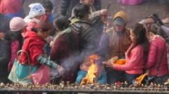 Pilgrim Family ligthing candles and inscence sticks,Dakshinkali,Nepal - stock footage