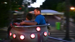 Father With Son Ride On Carousel at Night Carnival Stock Footage